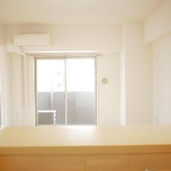 対面式のキッチンから見る明るいリビング (※写真は4階の同間取り別部屋のものです)
