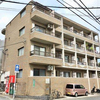 坂の手前にある4階建てのマンション。