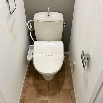 ウォシュレット付きトイレ。テラコッタ風な床とグレージュのクロスがお洒落。