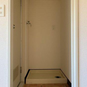 洗濯機置場は白い引き戸を開けたところに。お風呂場のすぐ手前だから便利!