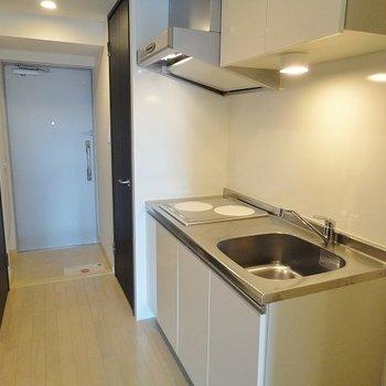 キッチンは掃除しやすいIH2口。(※写真は10階の反転間取り別部屋のものです)