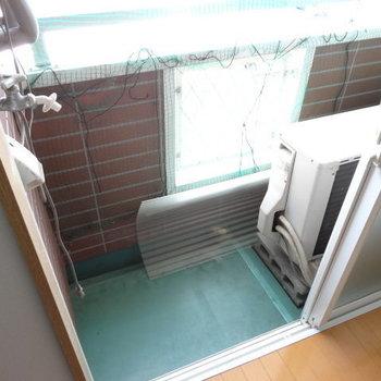 バルコニーに洗濯機置場。室外機があるので出るスペースはないかな。