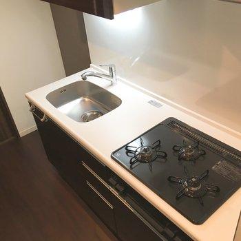 キッチンは3口コンロ、お料理が趣味になるかも。※写真は5階の反転間取り別部屋のものです