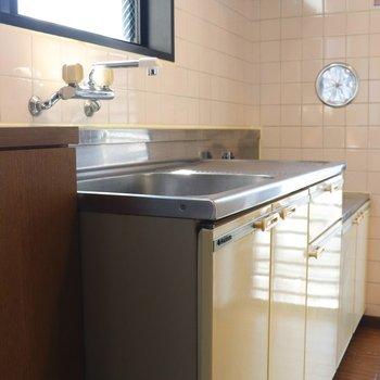 ベージュ基調のキッチン、壁もベージュのタイル張り
