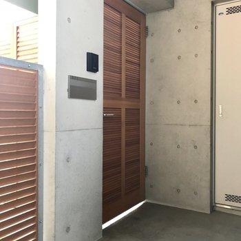 そしてこちらが共用部からアプローチへの扉。木目の格子がかっこいい!