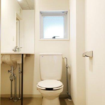 【上階】トイレは洗面台の隣にあります※写真はクリーニング前のものです