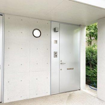 スタイリッシュな銀の玄関ドア。玄関横に自転車を置くことができます。