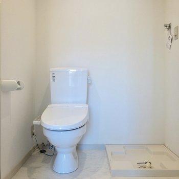 温水洗浄便座付きのトイレ。横には洗濯機置場。