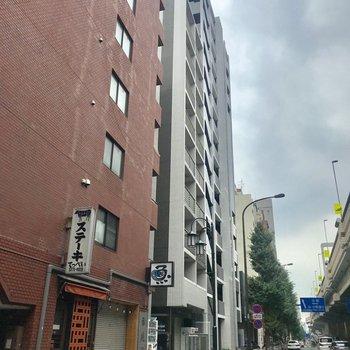 赤茶の建物の右隣に。大通り沿いです。