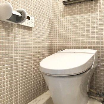 洗面所は一面タイル張り。トイレには温水洗浄便座がついています。