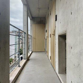 共用廊下。クリーム色のドアが柔らかな印象です。