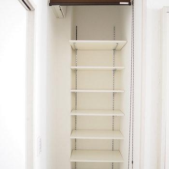 玄関横に可動式の棚があります。ロールカーテンもついているので、靴を置いてもいいですね。