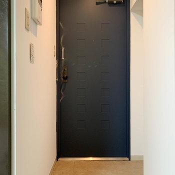 洗濯機置き場の左、木のスライドドアを開けると玄関。