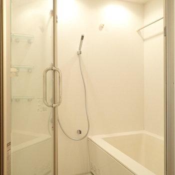 ガラスの扉に、2つのシャワーヘッドがある浴室。