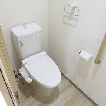 トイレは引き戸。そして手すり付きのユニバーサルデザインを感じます(※写真は2階の同間取り別部屋のものです)