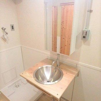 続いてサニタリー。木のぬくもりを感じるオリジナルの洗面台。その隣には洗濯機置場。