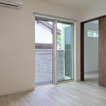 エアコン付き。バルコニーに通じる窓は掃き出し窓です。(※写真は1階の反転間取り、角部屋のものです)