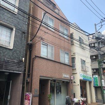 1階がお店の赤レンガ風の建物です