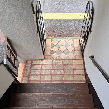 階段は木が敷かれて、上がり口はかわいいタイル&門扉で。