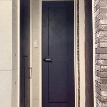 キッチンの後ろ、収納やサニタリーへ続く扉があります。