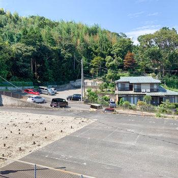 共用部からの眺望。お隣の月極駐車場や木々が見えます。