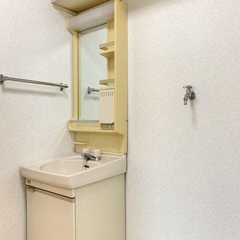 洗面台の隣には洗濯機置場。上部に収納付き。