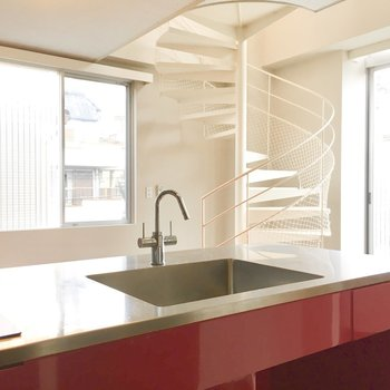 1階】赤いキッチンからは白の螺旋階段。