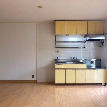 黄色いキッチンに立つキミ