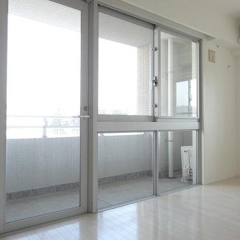 大きな窓が特徴です。お部屋から見える景色は青空。(※写真は9階の同間取り別部屋のものです)