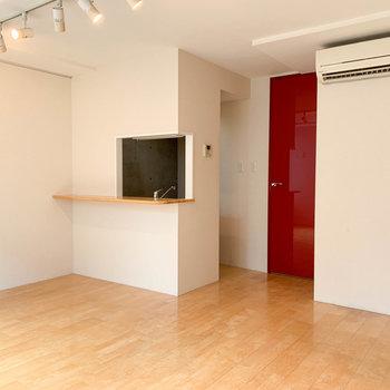 窓の逆側にはキッチンと、廊下へ続く赤い扉。