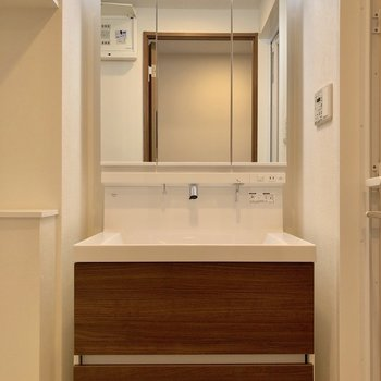 廊下の先に進むと、鏡部分が収納になっている洗面台※写真は5階の同間取り別部屋のものです