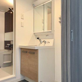 脱衣所の洗面台の扉はウッド調のもので柔らかい雰囲気に♪