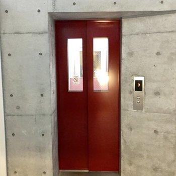 コンクリートの中にある、可愛い赤いエレベーター
