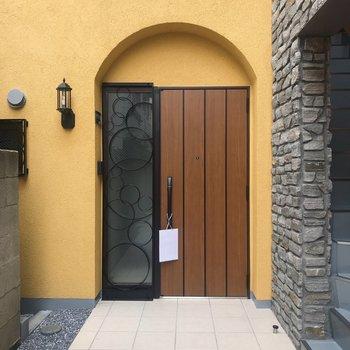 黄色で映えてる木の玄関ドアがお出迎え