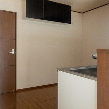 【LDK】キッチン後ろのスペースは広々。天井付近には収納スペースが。※写真は通電前のものです