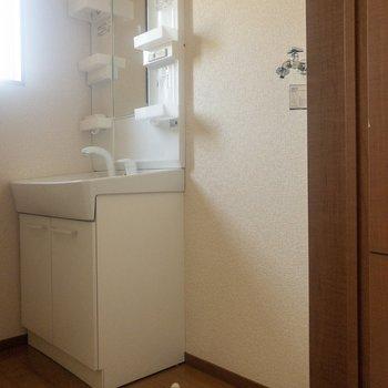 洗面台と洗濯機置き場。洗面台には収納がいっぱい。※写真は通電前のものです