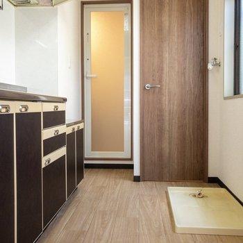 木目調の扉が素敵。トイレの前に洗濯機置場があります