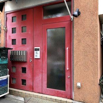 入り口は八百屋さんの隣にある真っ赤な扉