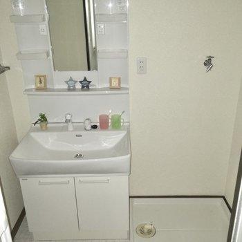 サニタリー入るとすぐきれいな洗面台。洗濯機置場はおとなり。(※写真の小物は見本で、フラッシュ撮影をしています)
