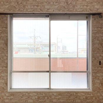 絨毯の洋室の窓から続くガーデンバルコニー。