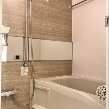 浴槽は温かみのあるブラウン。横長の鏡が特徴的です。