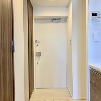 玄関は白いライトで明るい。※写真は4階の同間取り別部屋のものです