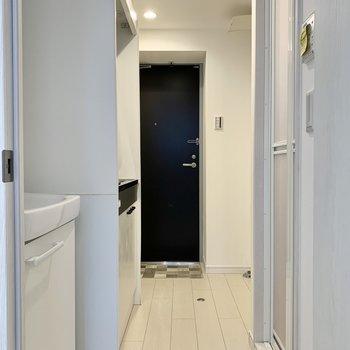 右手前からバス・トイレ、左手前から洗面台、キッチンです。※写真は4階の同間取り別部屋のものです