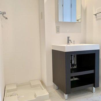 洗濯機はシンプルな洗面台の隣