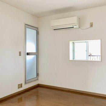 【洋室】こちらにも窓があります。左の扉はお風呂場へつながっています※写真は通電前のものです