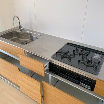 キッチンは3口コンロにグリルつき。収納も充実しています。器も入りそう◎