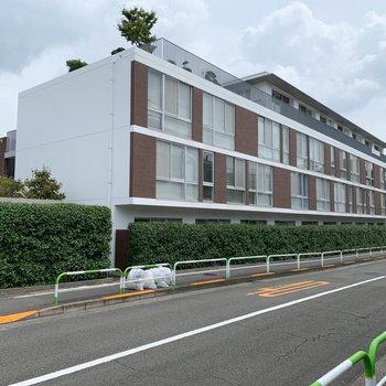 道路沿いの、クールな外観のマンション。