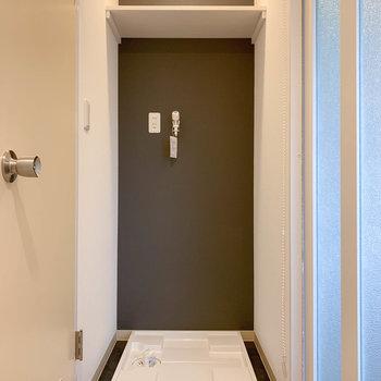 廊下の角に洗濯機置き場があります。ちなみにブラインドで隠すこともできます。