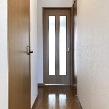 おりてきて、玄関から。手前にサニタリー。※写真は1階の同間取り別部屋のものです