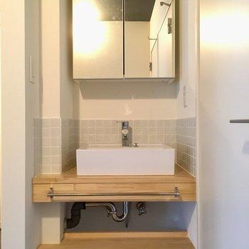 洗面台は大工さんお手製。鏡は扉になっていて、開けると収納が◎